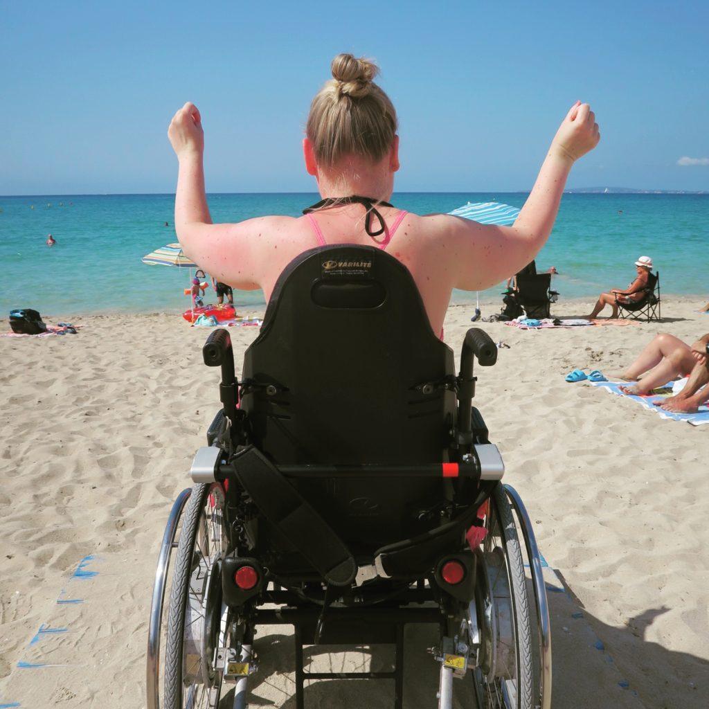 Manon in haar rolstoel op het strand.