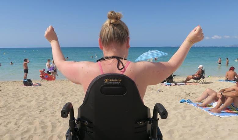 Manon op het strand in haar rolstoel.