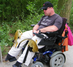 Man in een elektrische rolstoel in de Apenheul met twee apen op zijn schoot.