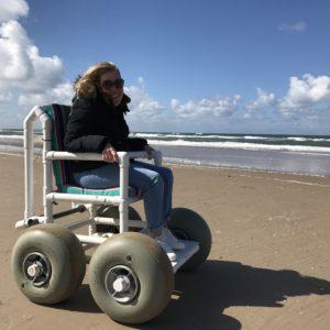 Manon in de geleende strandrolstoel in Egmond aan Zee.