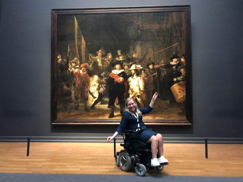 Manon in haar rolstoel voor het schilderij de Nachtwacht in het Rijksmuseum in Amsterdam.