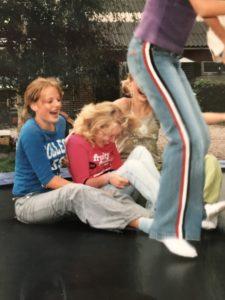 Een lachende Manon met haar vriendinnen op de trampoline tijdens een feestje van haar vriendin. Manon zit op de trampoline en wordt vastgehouden door 2 vriendinnen terwijl de andere 3 meiden springen.