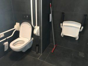 Het toilet en douchestoeltje van de aangepaste hotelkamer in Golden Tulip Keyser Breda Centre.